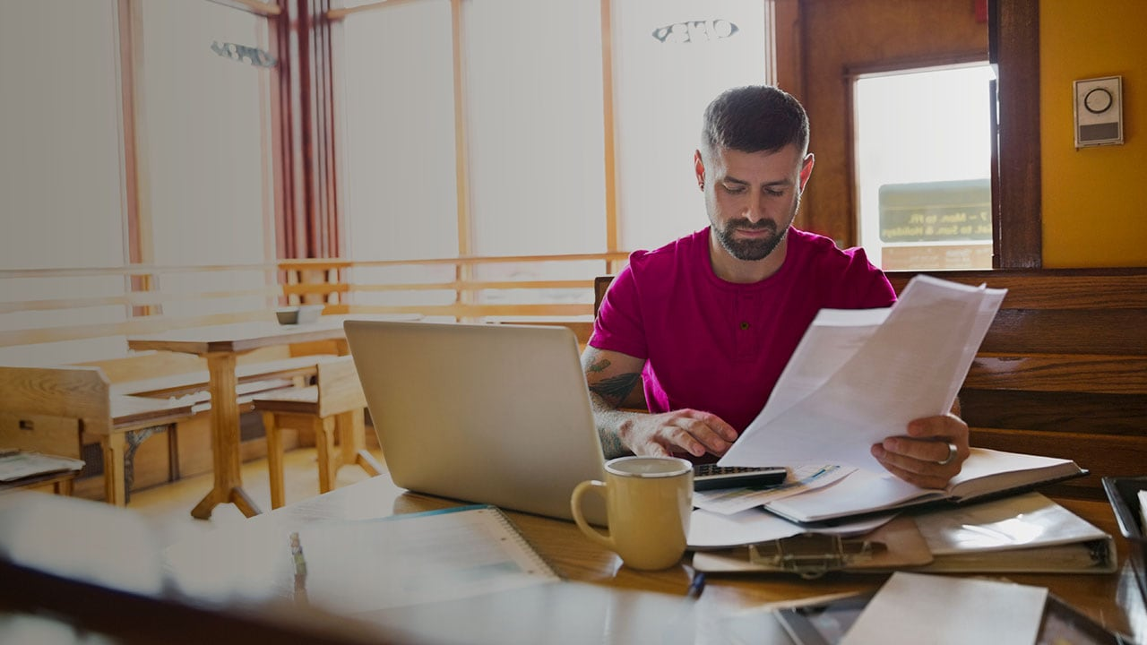 Man looking at paperwork and sitting at a table with a laptop