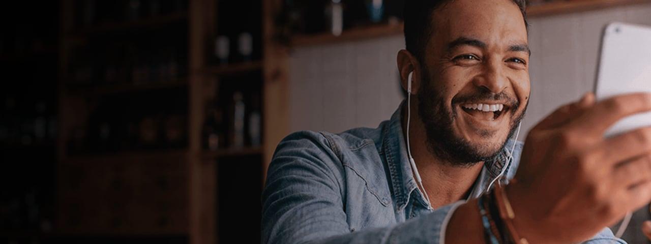Imagen en primer plano de un hombre sonriendo al dispositivo que sostiene en sus manos.