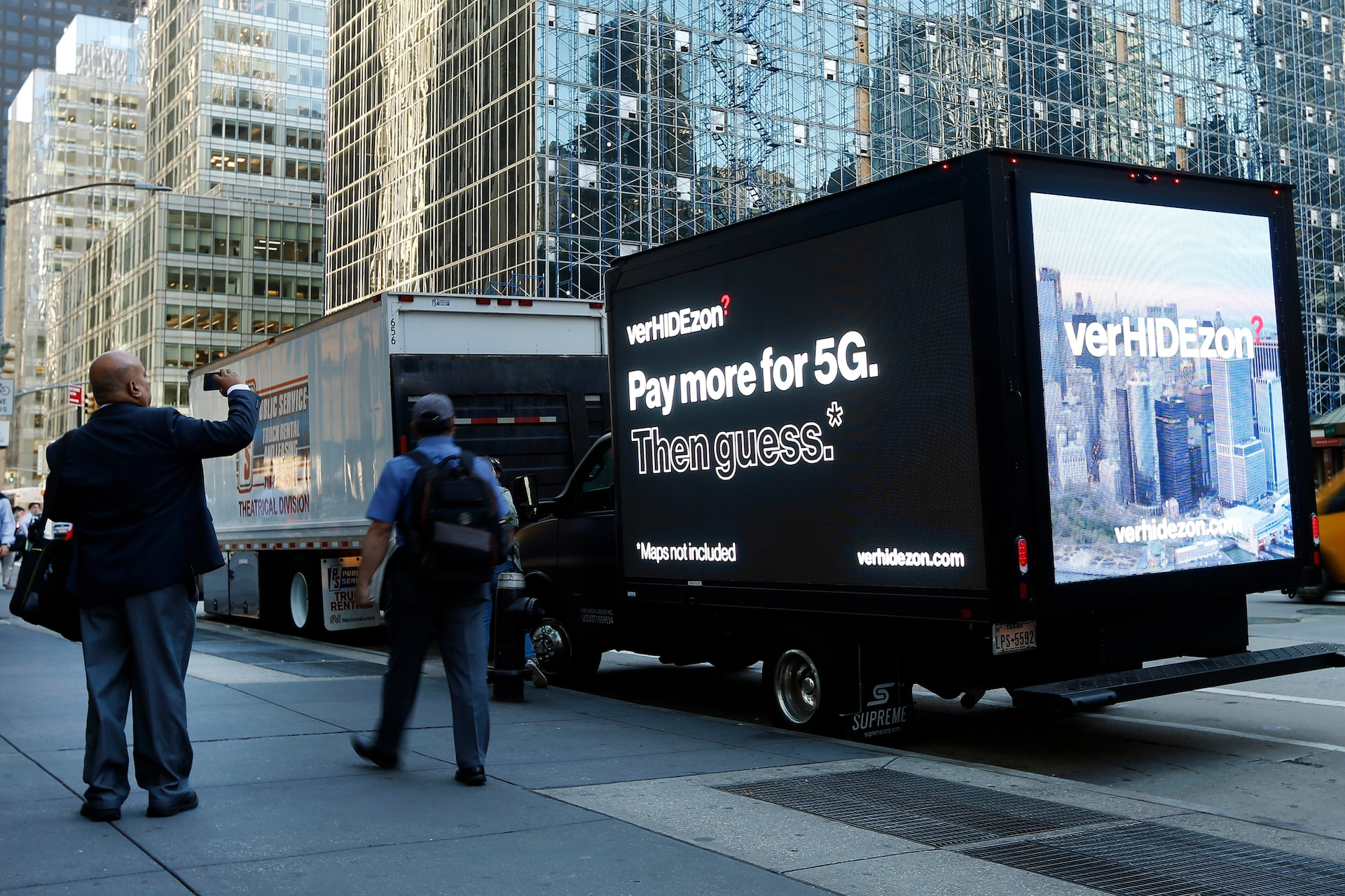 "An early morning commuter snaps a photo of the ""VerHIDEzon"" digital billboard as it takes to the streets of New York City to show a real representation of what Verizon's 5G marketing should look like — Verizon is charging their customers more for 5G and won't tell them where they can use it."