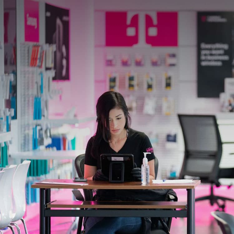 T-Mobile employee working in a T-Mobile retail store