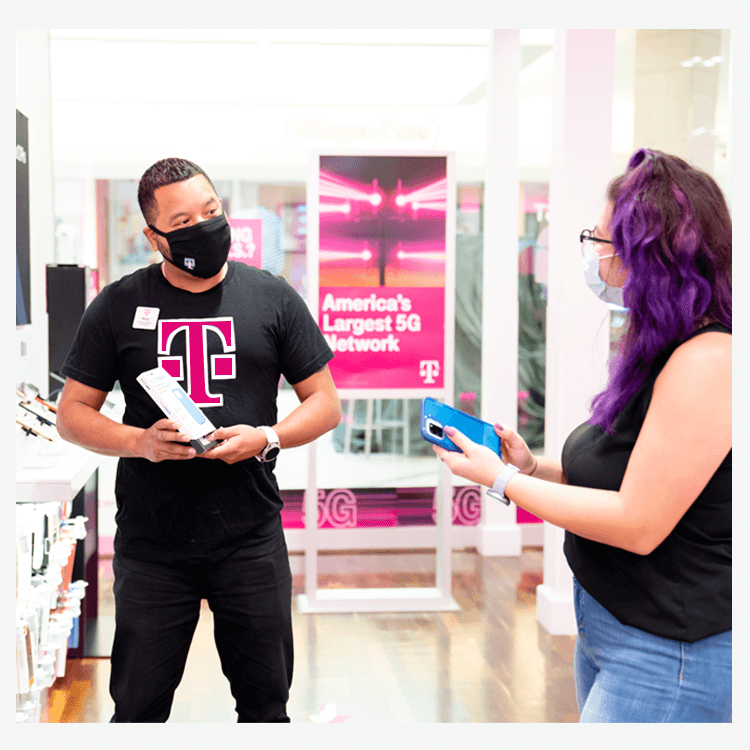 T-Mobile man talking with client about cellphones.