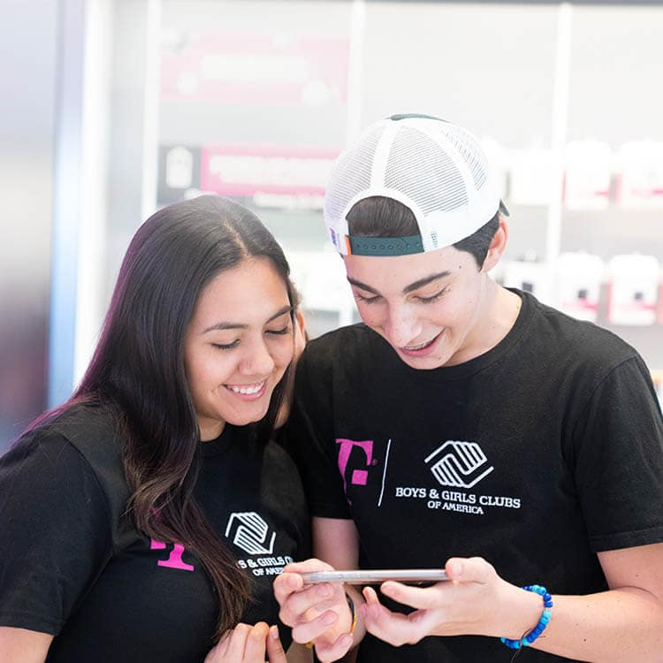 Two students use a smartphone in a T-Mobile store.