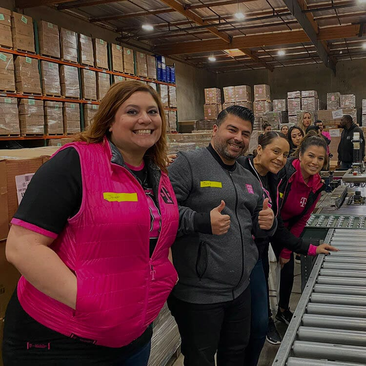 A group of T-Mobile employees smiling while volunteering.