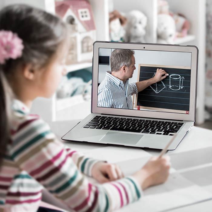 Un estudiante viendo a un maestro en una laptop y tomando notas.