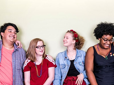 A group of people standing in front of a white wall and smiling.