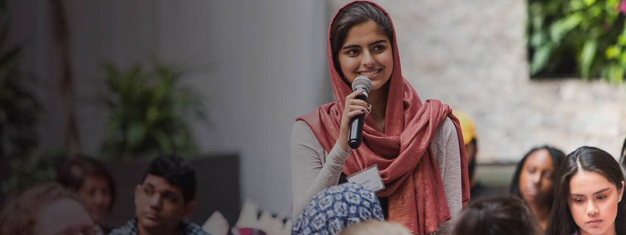 Young Indian woman speaks to a group of people during changemaker challenge