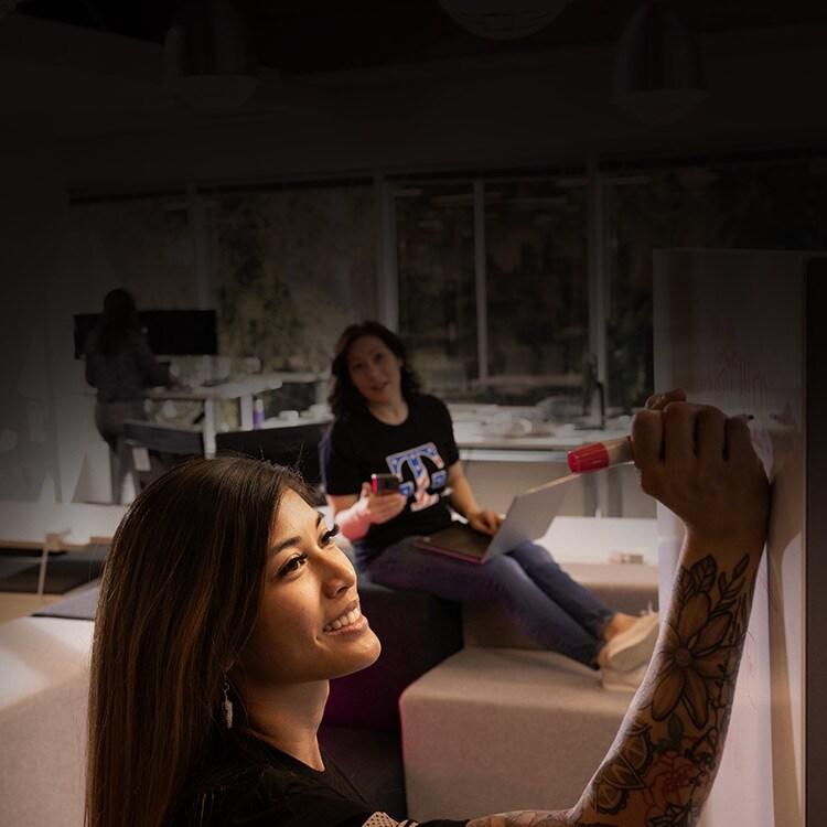 Mel Sobrenilla escribiendo en una pizarra blanca con una colega en el fondo.