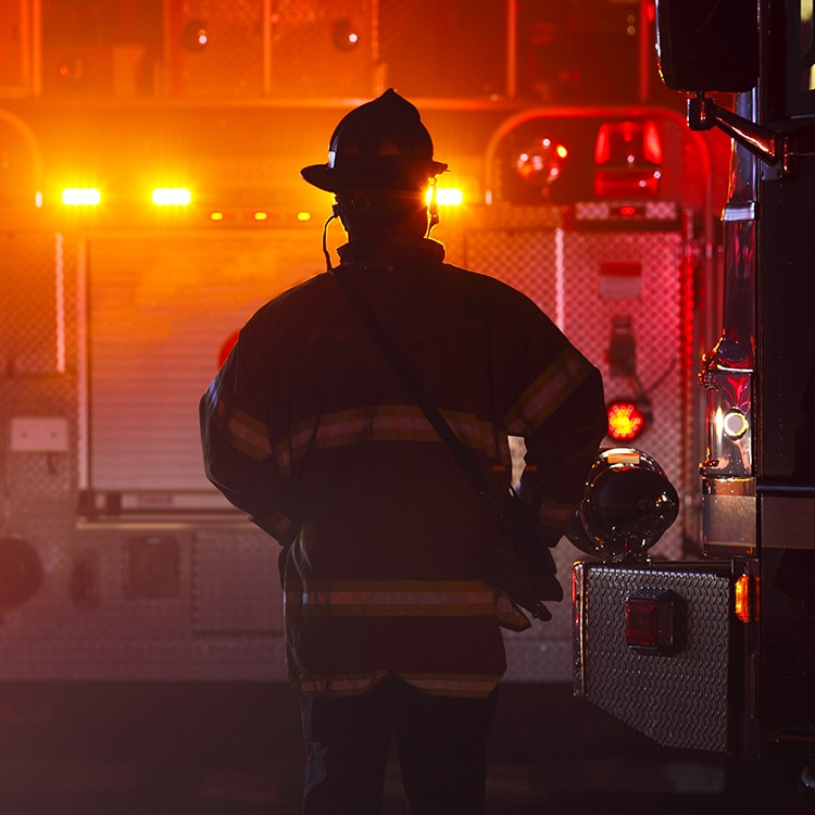 Firefighter standing in front of a fire truck with lights on