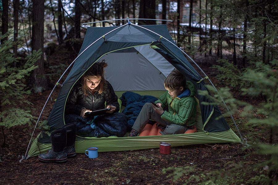 two kids watching on their devices in a tent