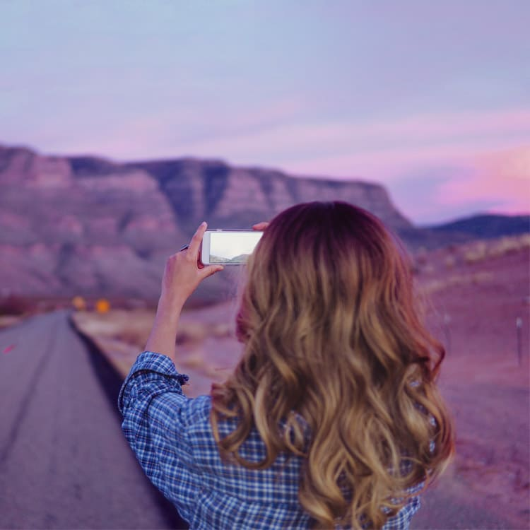 Woman taking photo on scenic road at sunset
