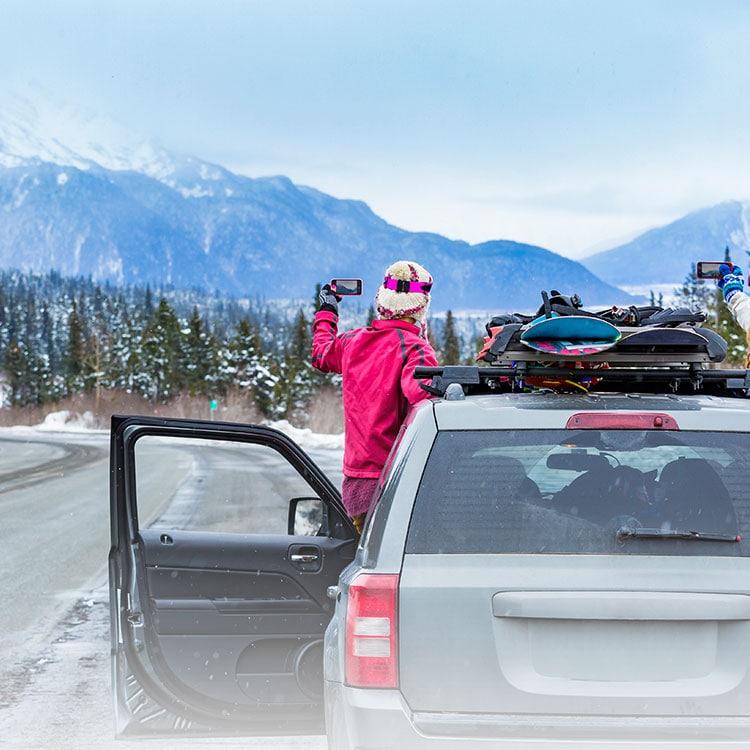 Mujer en una ruta nevada, inclinándose fuera de un SUV para tomar la foto de una montaña con el teléfono