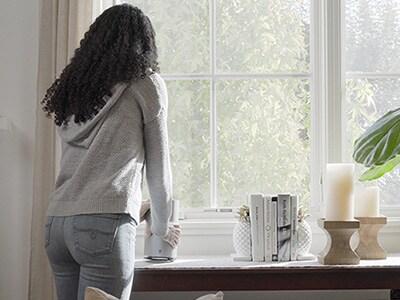 Mujer colocando la puerta de enlace Wi-Fi 5G cerca de una ventana.