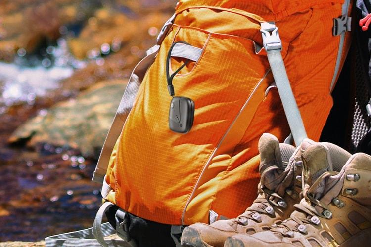 Sync-up tracker sujetado a una mochila apoyada cerca de botas de excursionismo y un arroyo.