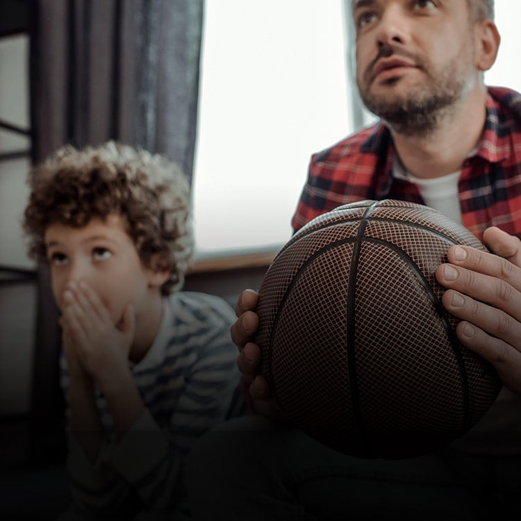 Man and son watching basketball together